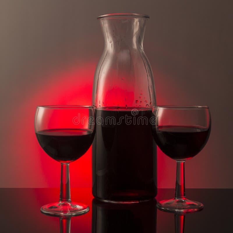 两杯红葡萄酒和一个玻璃瓶在黑玻璃bo 免版税库存图片