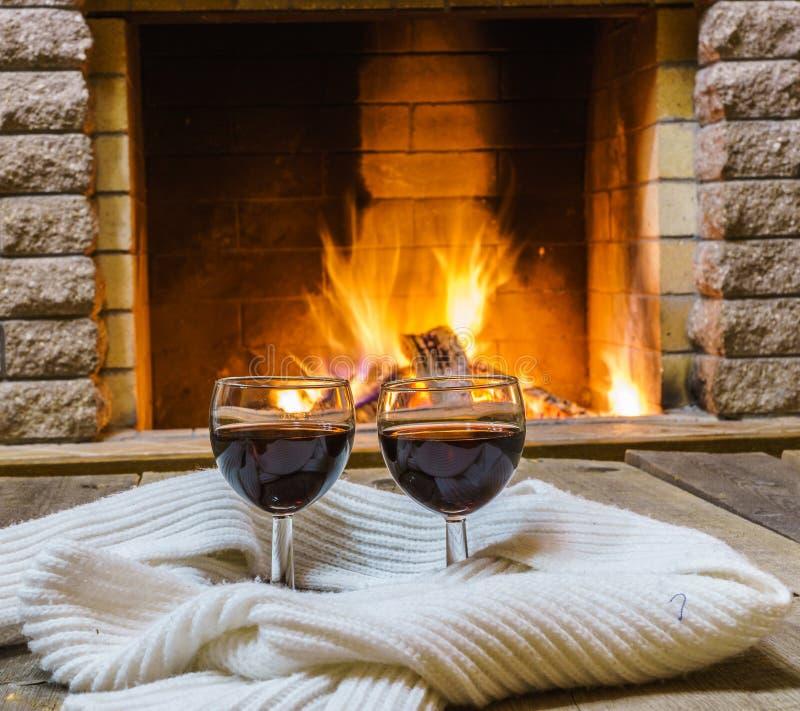 两杯红葡萄酒和羊毛事临近舒适壁炉 免版税库存照片
