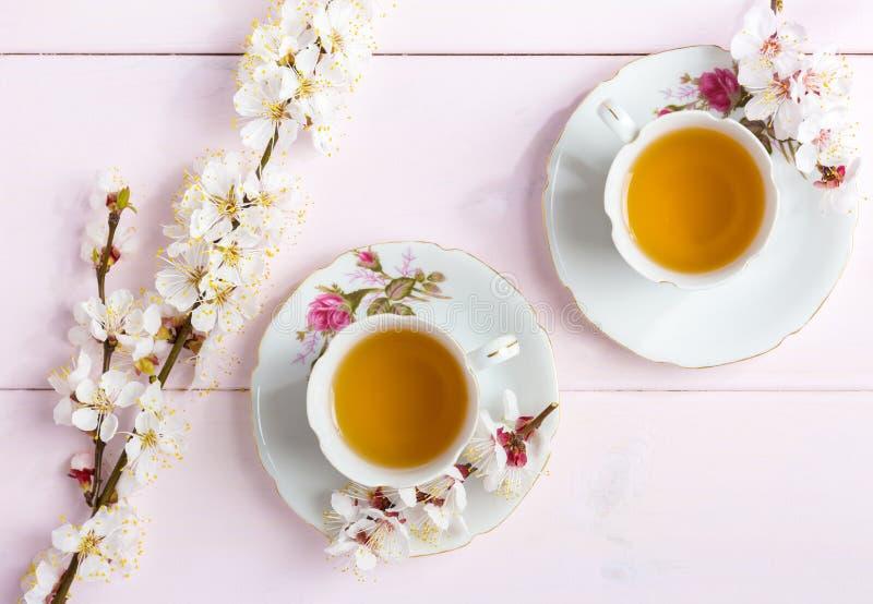 两杯茶和春天一个杏子的花绽放在一张浅粉红色的木桌上的 免版税库存照片
