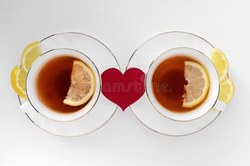 两杯茶用柠檬和红心在白色背景 关系,在爱的愉快的夫妇的概念 免版税图库摄影