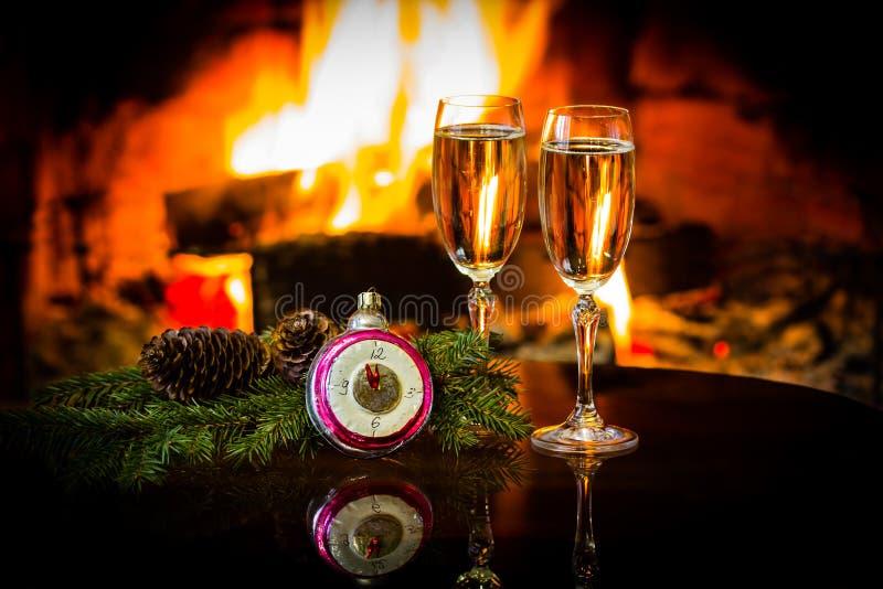 两杯酒和圣诞节新年装饰,壁炉 免版税库存照片