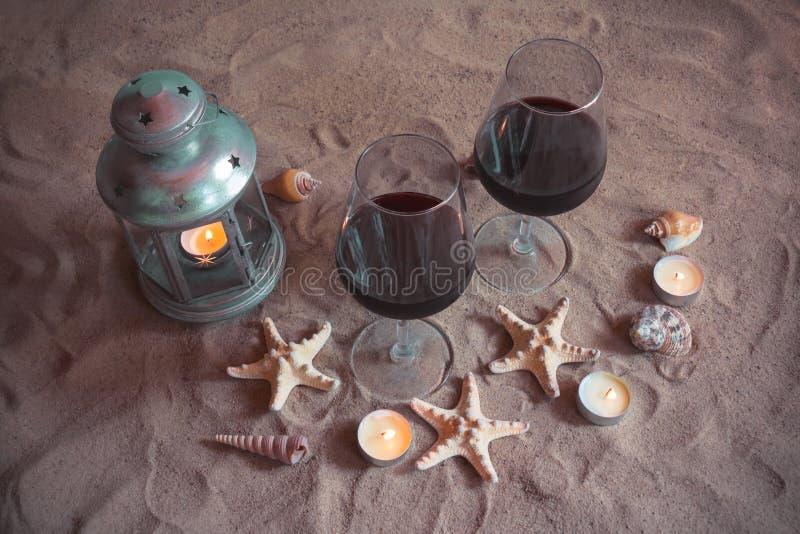 两杯酒,蜡烛,灯笼,壳,海星 免版税图库摄影