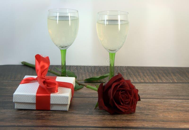 两杯香槟、红色玫瑰和礼物盒在一张木桌上 免版税库存照片