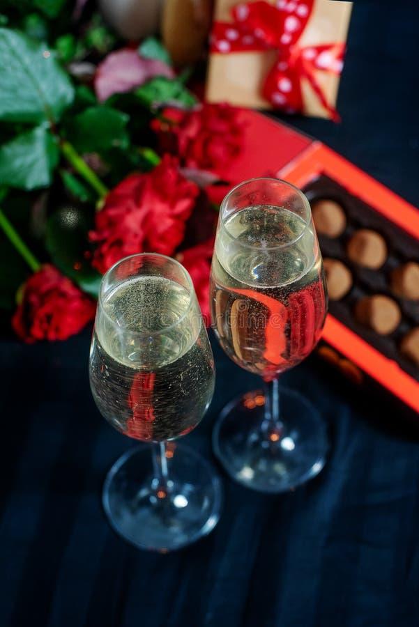 两杯香槟、英国兰开斯特家族族徽和糖果在黑背景 免版税库存图片