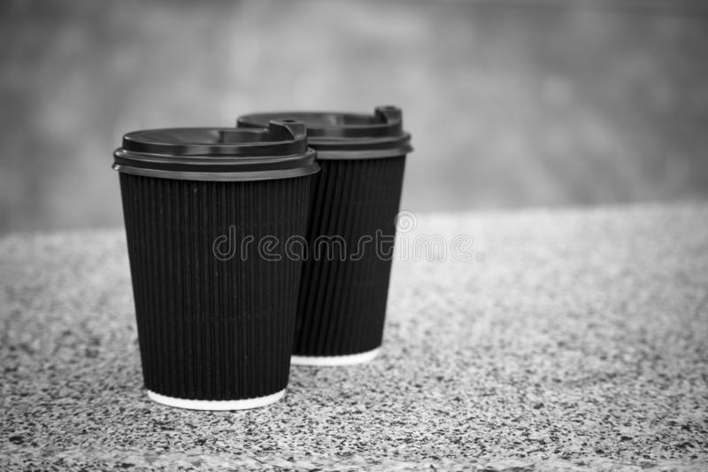 两杯黑一次性咖啡与盒盖的在石栏杆站立 库存照片