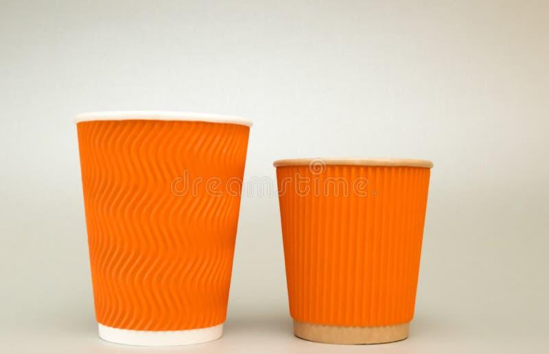 两桔子挖沟了咖啡立场的纸杯在白色背景,大和小 库存照片