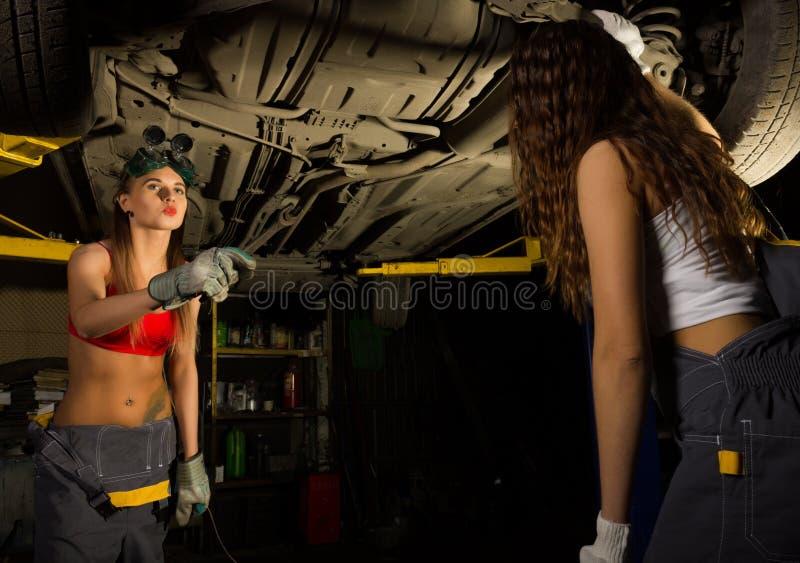 两检查在汽车修理店的美丽的年轻女性技工汽车 性感的技工 库存图片