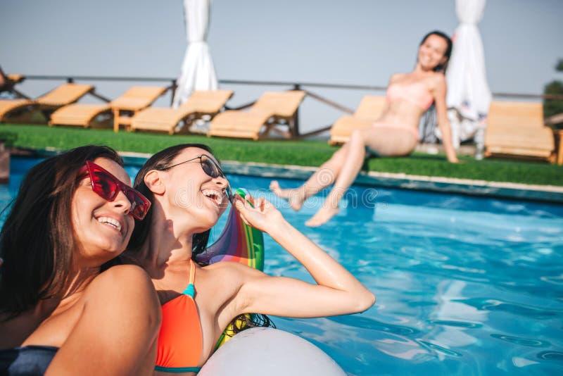 两模型的图片一起坐在游泳池的浮游物 他们微笑并且看第三个 她坐在边缘  免版税库存图片