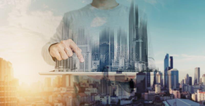两次曝光、一个人使用数字式片剂的和现代大厦全息图 房地产事务和建筑技术概念 免版税库存图片