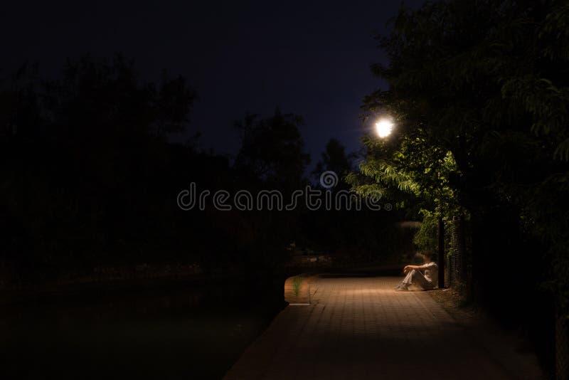两次曝光坐在黑暗的街道的人夜场面在光下 在路的后退男性剪影  库存图片