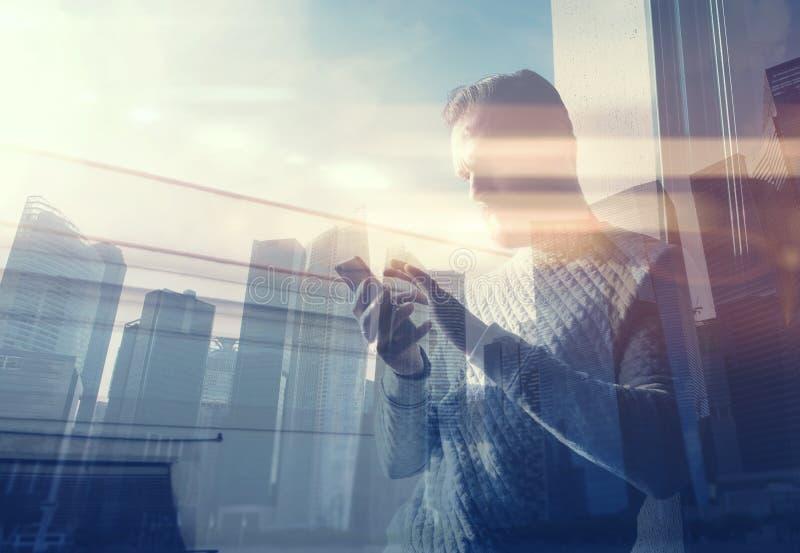 两次曝光照片人触摸屏智能手机 图片有胡子的贸易商经理在现代顶楼 当代城市 免版税库存图片