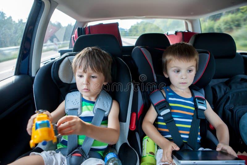 两汽车座位的男孩,旅行在汽车和使用与玩具和 库存照片