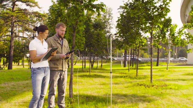 两测量噪声级的生态学家在高速公路附近 免版税库存照片