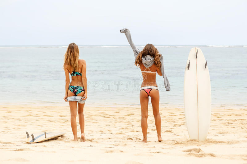 两海滩的美丽的运动的冲浪者女孩 库存图片