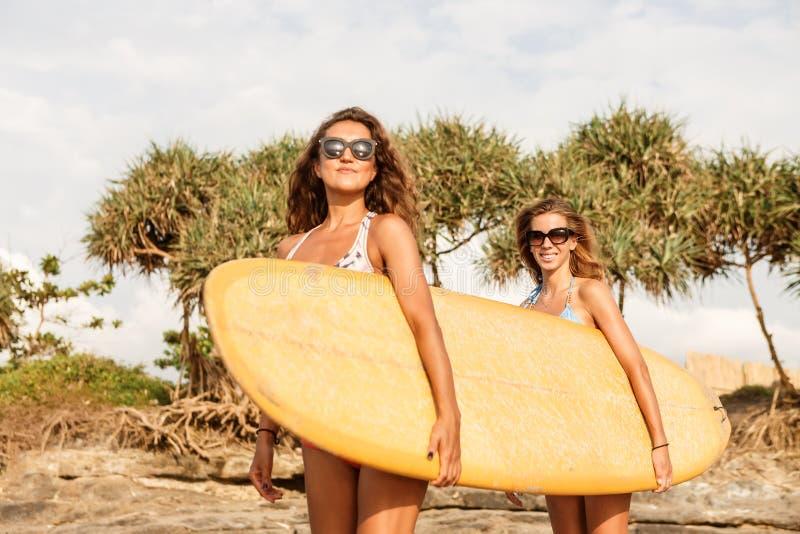 两海滩的美丽的运动的冲浪者女孩 免版税图库摄影