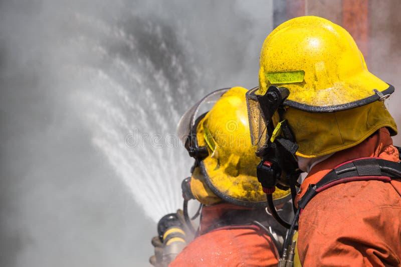 两消防队员在射击的盔甲和氧气面罩喷洒的水中 免版税图库摄影