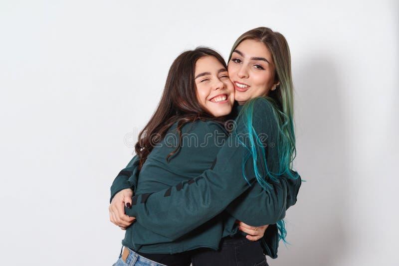 两滑稽的愉快的妇女女友在白色背景拥抱 妇女的友谊,姐妹,青年时期 免版税库存图片