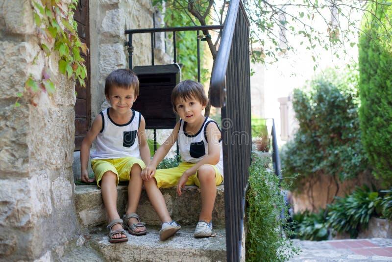 两漂亮的孩子,男孩兄弟,坐台阶为 库存照片