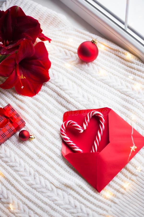 两焦糖藤茎以心脏的形式在红色信封的在白色被编织的格子花呢披肩围拢与冬天装饰 免版税库存图片