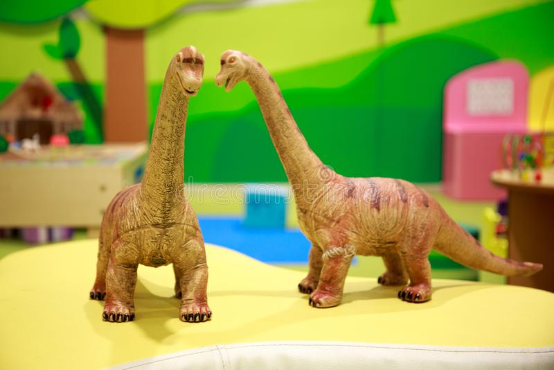两玩具恐龙愉快地谈话对于儿童` s操场 库存图片