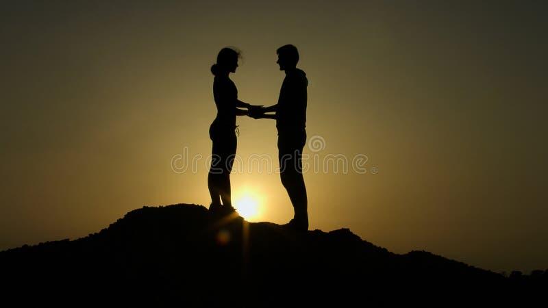 两现出轮廓握手在山顶部反对日落,一起克服 图库摄影