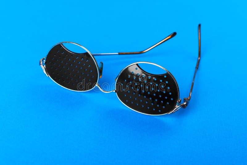 两玻璃的不同类型在蓝色背景的 医疗概念 顶视图 针孔黑镜片帮助松弛疲倦的眼睛Iso 免版税库存图片