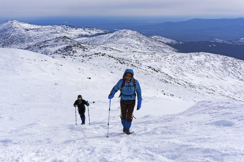 两登山人攀登积雪的山坡 库存图片