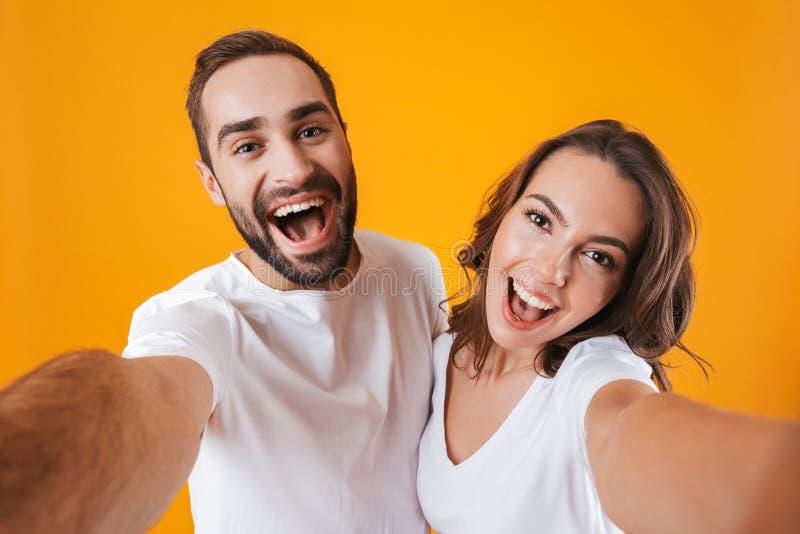 两白种人人男人和的妇女画象微笑,当拍selfie照片,被隔绝在黄色背景时 免版税库存照片