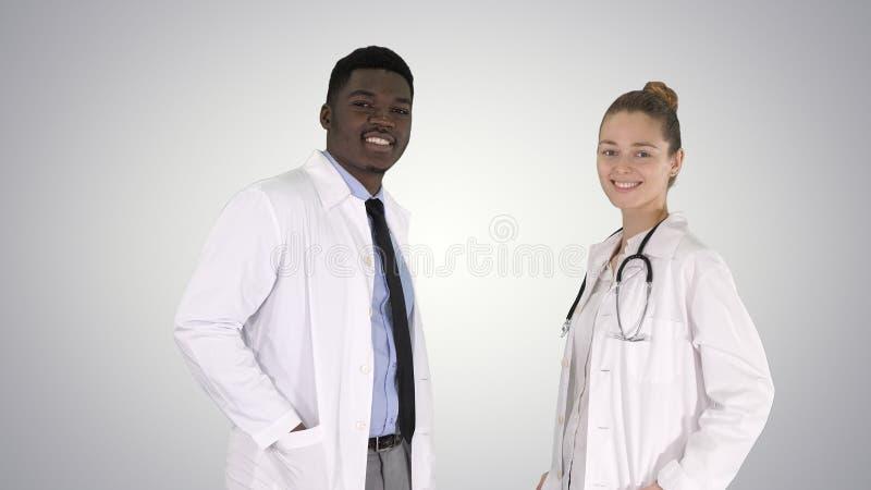 两白种人和浏览在梯度背景的照相机的美国黑人的微笑的医生身分 免版税库存照片