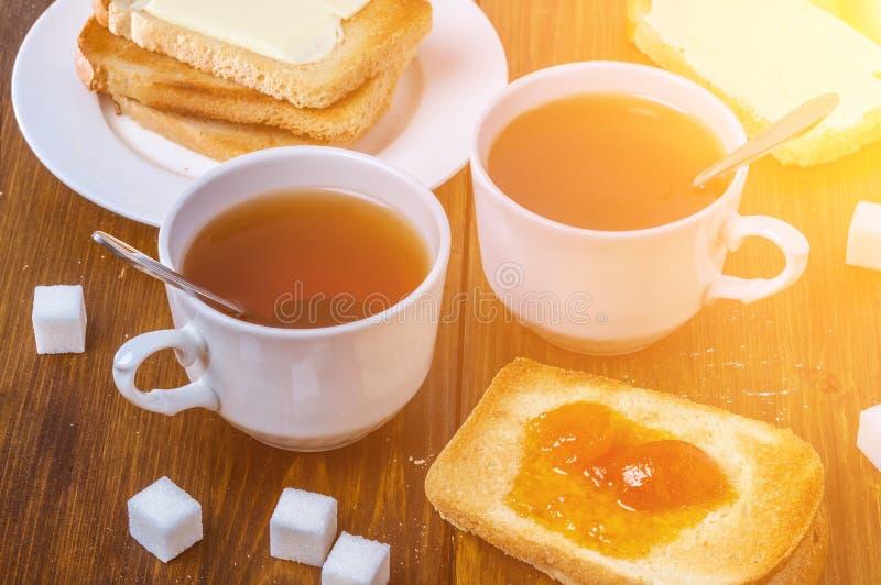两的浪漫早餐与杯子与敬酒的谋生的热的茶和樱桃果酱 图库摄影