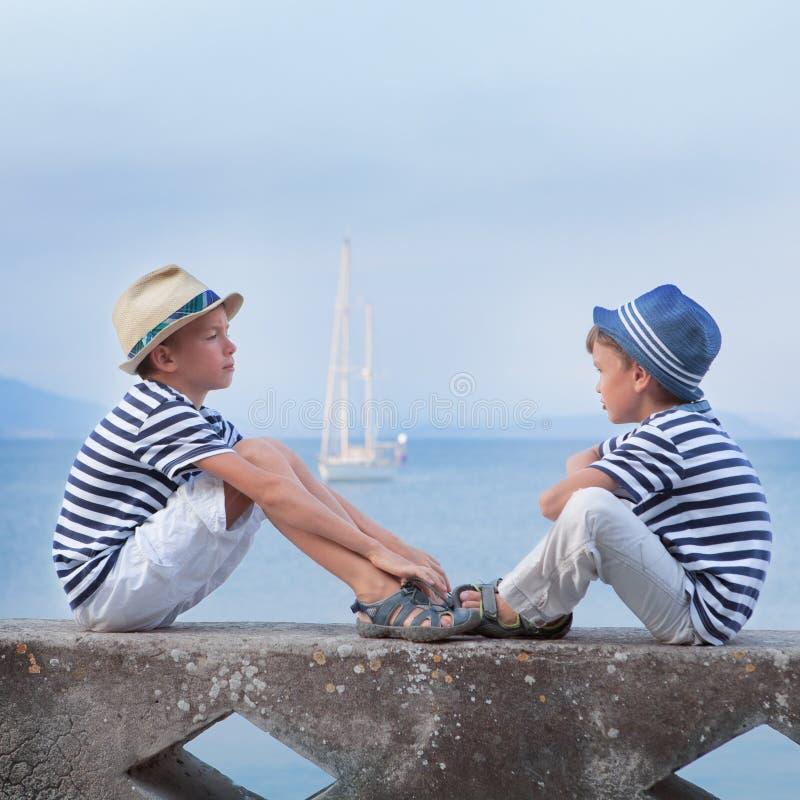 两相似的兄弟坐江边, 库存照片