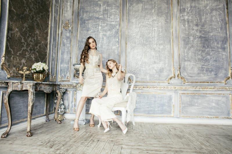 两相当双一起豪华房子内部的姐妹白肤金发的卷曲发型女孩,富有的青年人概念 图库摄影