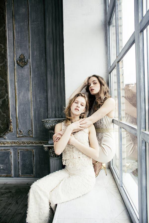两相当双一起豪华房子内部的姐妹白肤金发的卷曲发型女孩,富有的青年人概念 免版税库存图片