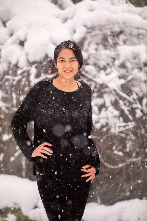 两种人种的青少年的女孩室外在享受降雪的冬天 图库摄影