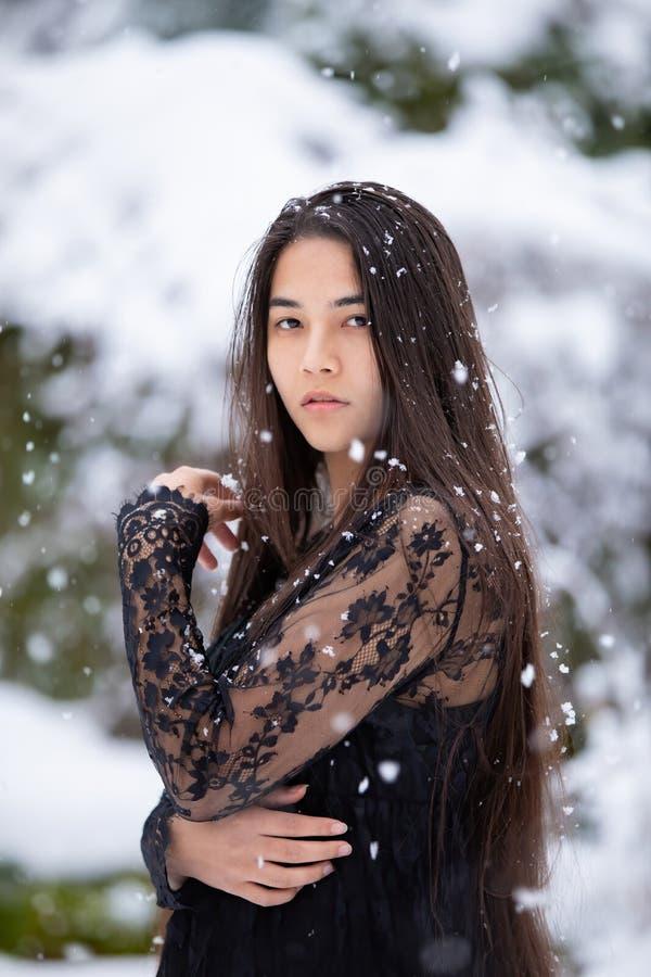 两种人种的青少年的女孩室外在享受降雪的冬天 免版税库存照片