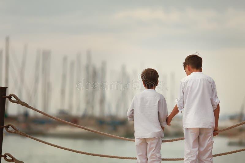 两站立在江边的相似的兄弟, 免版税图库摄影