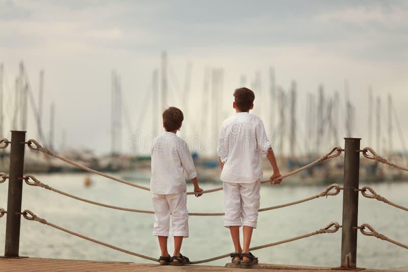 两站立在江边的相似的兄弟, 图库摄影