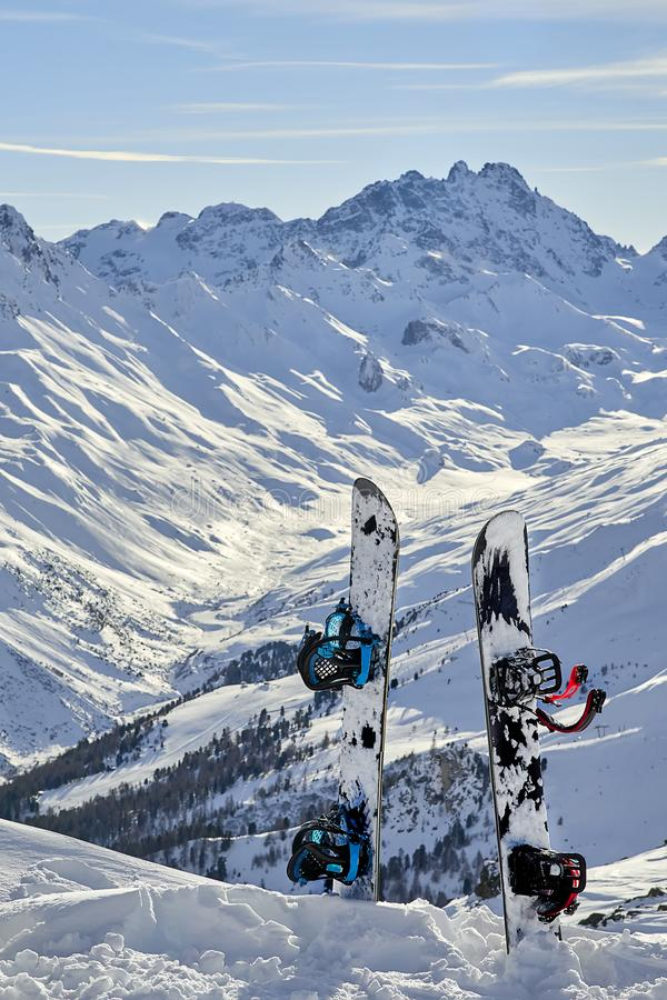 两站立的雪板挺直在山之间的雪在背景 库存照片
