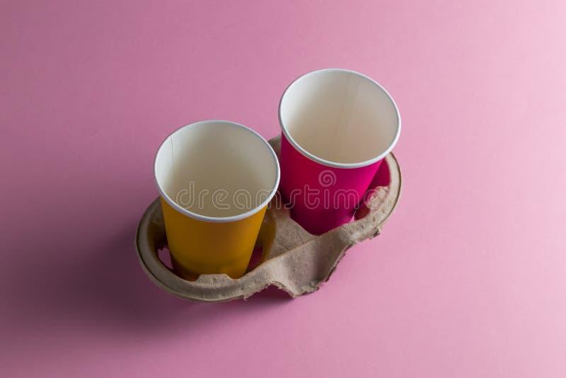 两紫罗兰色和在桃红色背景隔绝的黄色空的纸杯 免版税库存图片