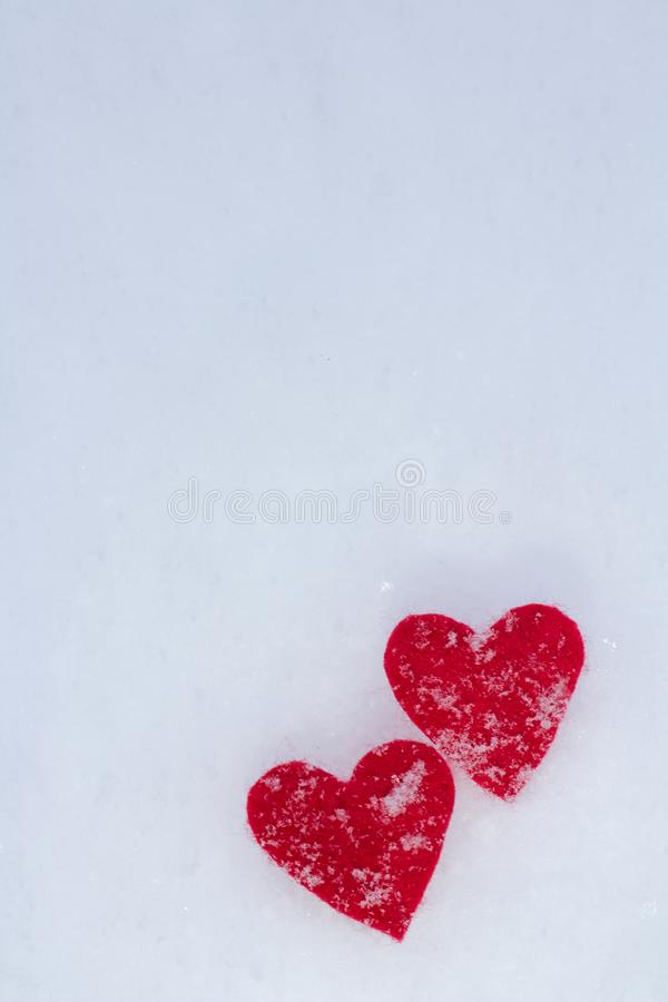两红心紧挨着搽粉与雪谎言在蓬松雪的冬天 免版税库存图片