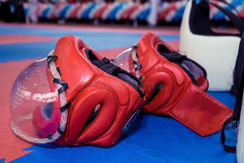 两红色与清楚的塑料面具和两件身体防护背心的空手道战斗的盔甲在地板上 免版税库存图片