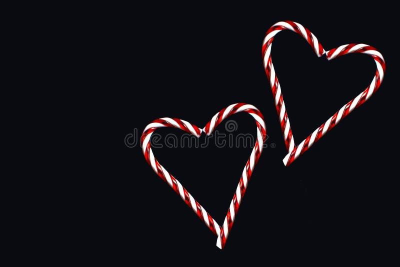 两红色和形成在黑背景的白色镶边传统圣诞节棒棒糖两心脏 库存图片