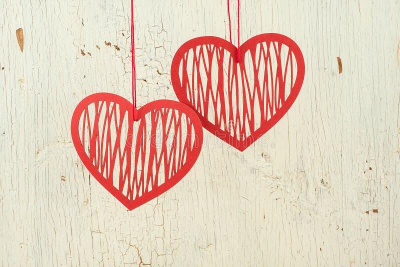 两红色在老白色木头的纸心脏 库存图片