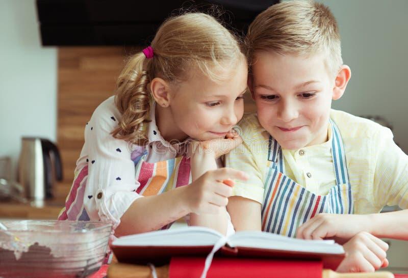 两美丽和探索recept的愉快的孩子在prepari前 免版税库存图片