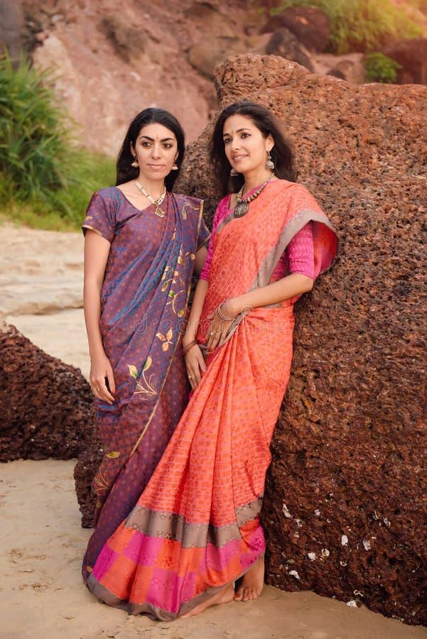 两美丽的传统莎丽服的美丽的印度妇女在日落 免版税图库摄影