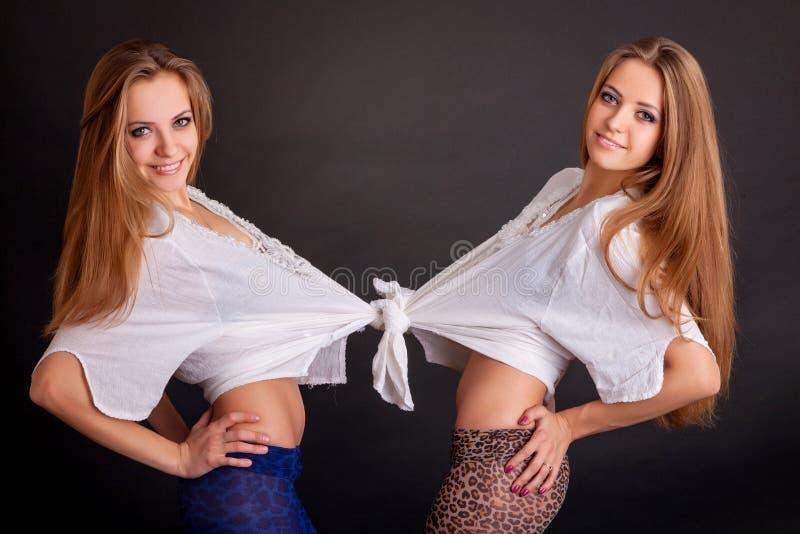 两美丽的女孩孪生,在黑色 库存图片