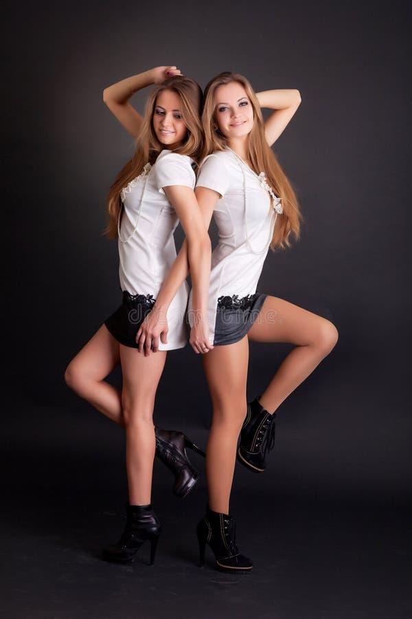 两美丽的女孩孪生,隔绝在黑色 免版税库存照片