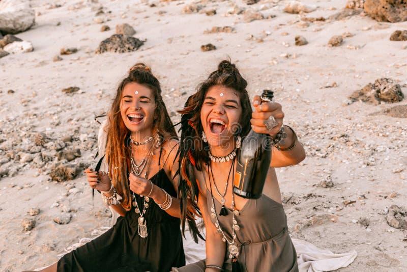 两美丽的年轻快乐的妇女获得乐趣在日落用香槟 库存照片