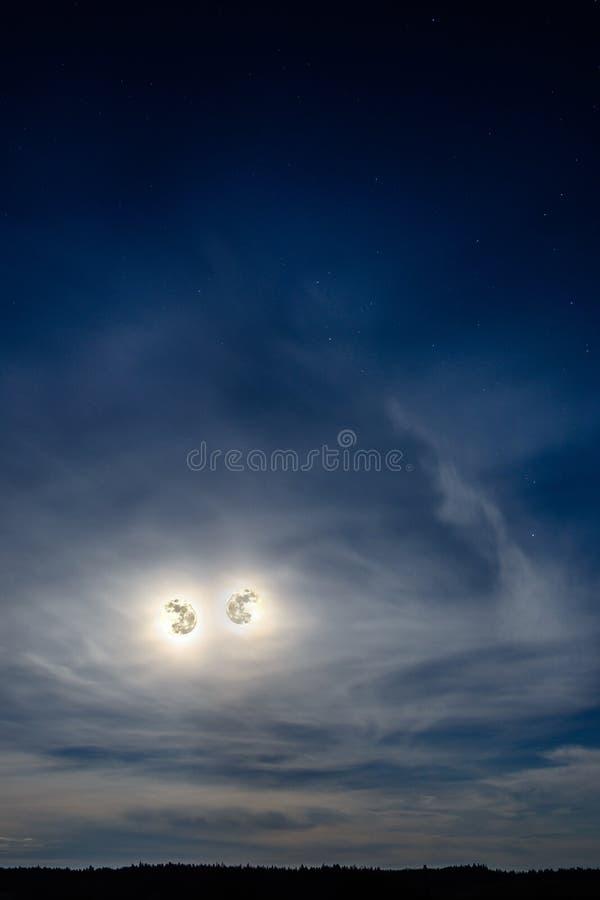 两美丽的月亮看我们从天空 库存照片