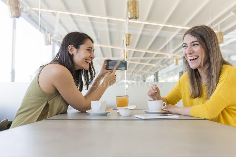 两美女食用早餐在餐馆 他们是笑和搜寻关于手机的信息 户内 库存图片